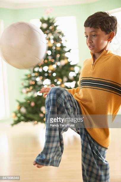 Boy Playing with Soccer Ball in Front of Christmas Tree