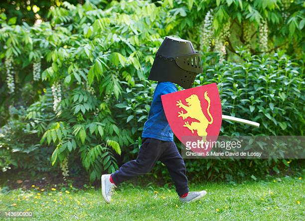 boy playing with sword in backyard - shielding stock pictures, royalty-free photos & images