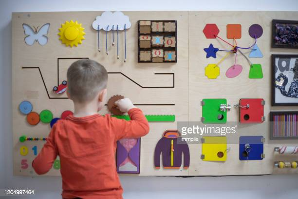 boy playing with the interactive board - montessori education stock pictures, royalty-free photos & images