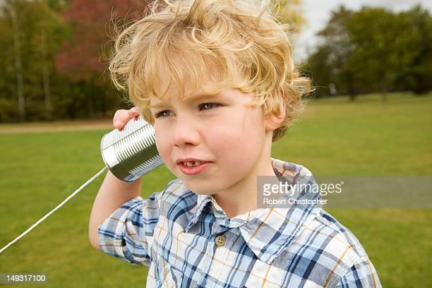 Junge spielt mit Blechdose Telefon können
