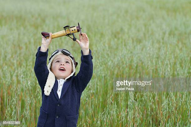 Boy playing with toy airplane in a field