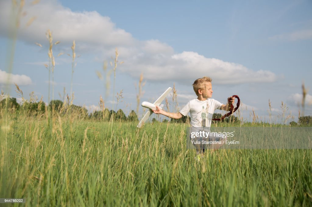 Boy Playing With Toy Airplane On Field Against Sky : Stock Photo