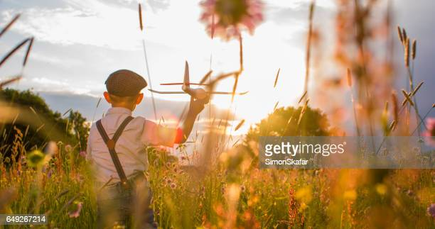 boy playing with toy airplane on meadow - flat cap stock pictures, royalty-free photos & images