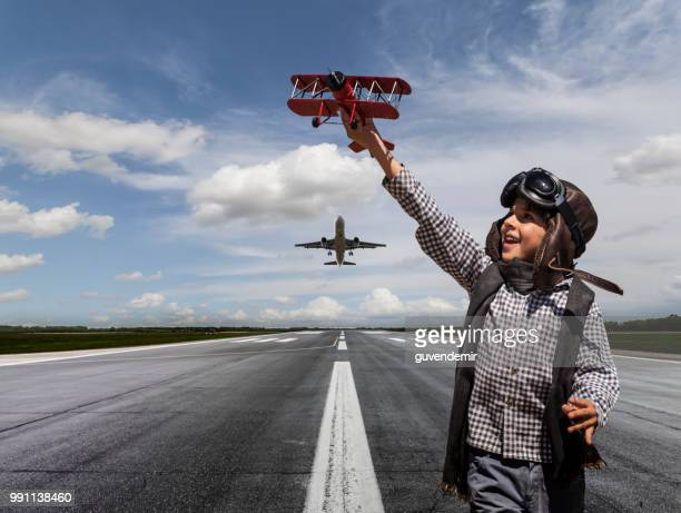 boy playing with toy airplane on runway - landing touching down stock pictures, royalty-free photos & images