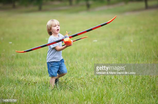 boy playing with toy airplane outdoors - saint ferme stock pictures, royalty-free photos & images