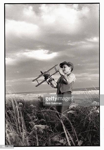boy (8-10) playing with toy airplane outdoors (b&w) - flat cap stock pictures, royalty-free photos & images