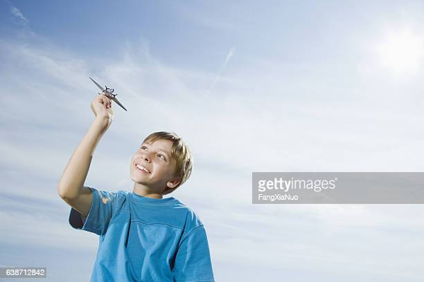 Boy playing with toy airplane outside with blue sky