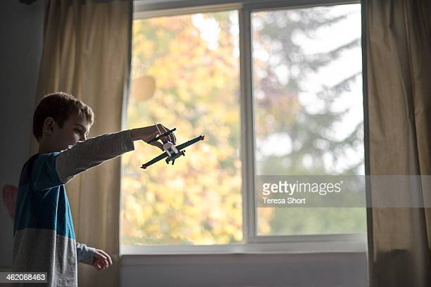 Boy playing with toy airplane