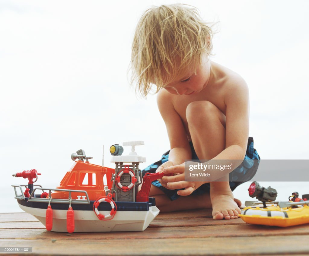 Boy (2-4) playing with toy boat, close-up : Stock Photo