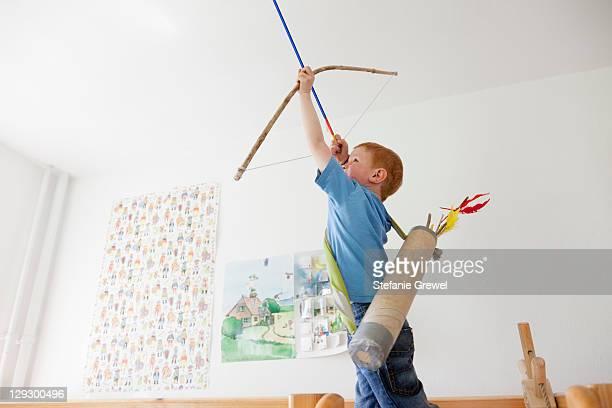 boy playing with toy bow and arrow - stefanie grewel stock-fotos und bilder