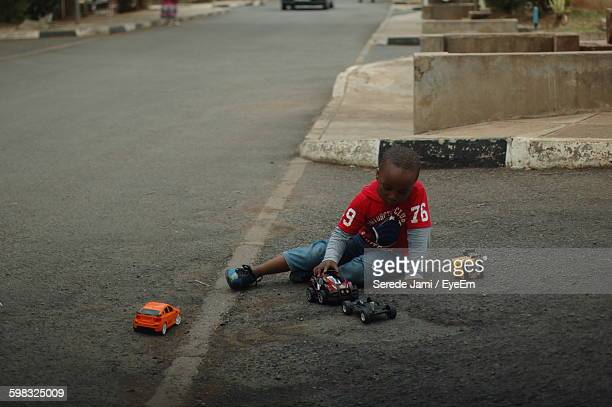 Boy Playing With Toy Car On Street
