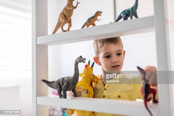 junge spielt mit spielzeug-dinosauriern - nur jungen stock-fotos und bilder