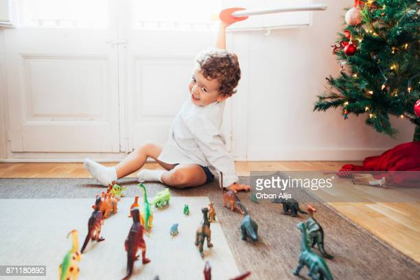 boy playing with toy dinosaurs - christmas past and christmas present stock pictures, royalty-free photos & images