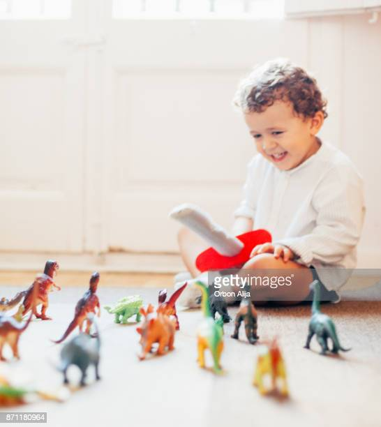 boy playing with toy dinosaurs - toy animal stock photos and pictures