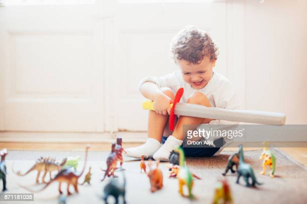 boy playing with toy dinosaurs - animal representation stock pictures, royalty-free photos & images