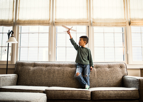 Boy playing with toy glider at home - gettyimageskorea