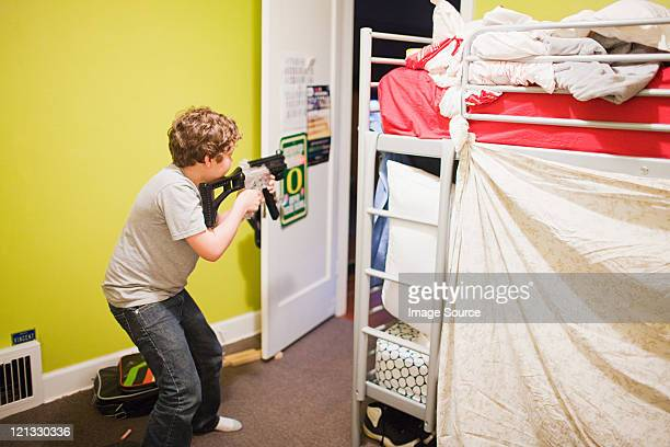 Boy playing with toy gun in bedroom