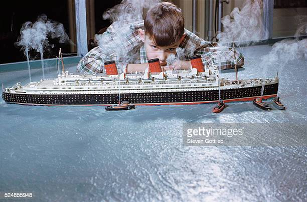 Boy Playing with Toy Ocean Liner