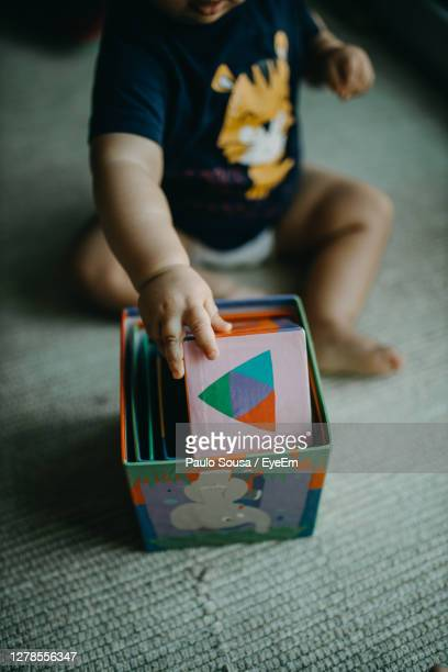 boy playing with toy on flooring - one baby boy only stock pictures, royalty-free photos & images