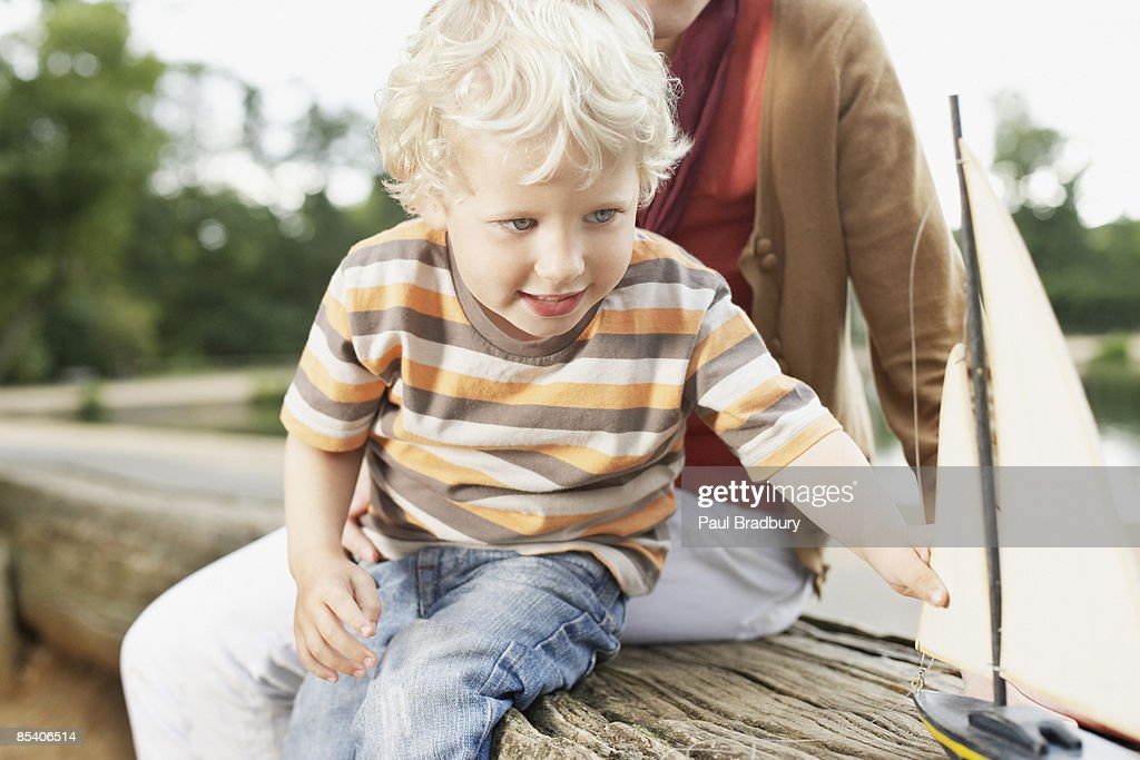Boy playing with toy sailboat : Stock Photo