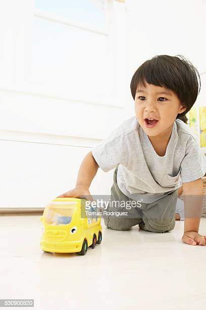 Boy playing with toy school bus