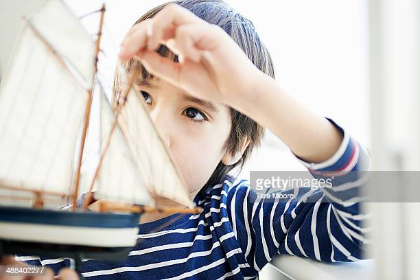 boy playing with toy ship