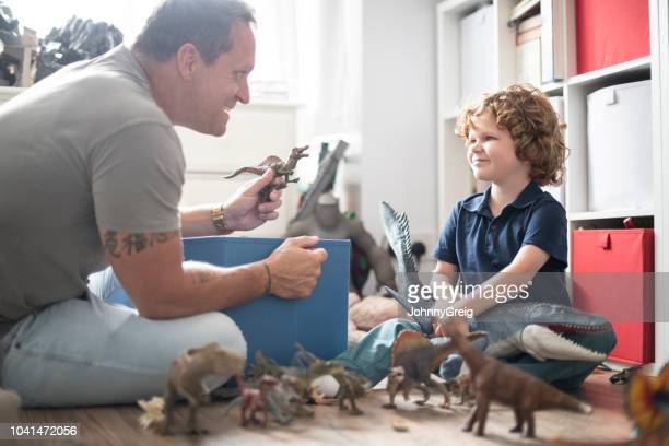 boy playing with toys with his father - dinosaur stock pictures, royalty-free photos & images