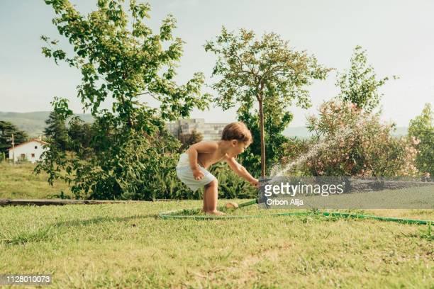 jungen spielen mit wasser sprinkler - gartenanlage stock-fotos und bilder