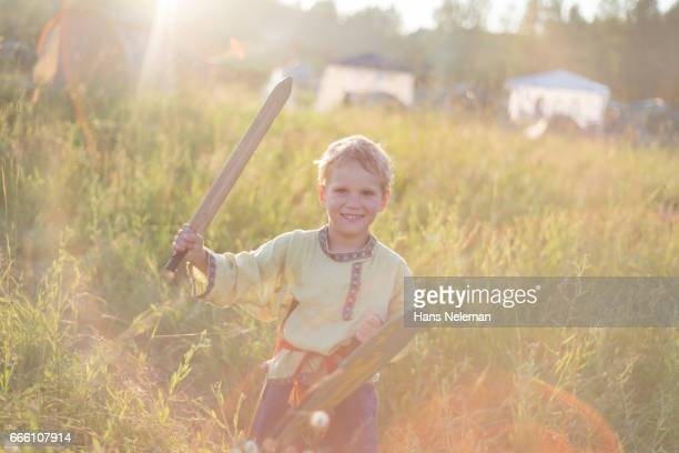 Boy playing with wooden sword and shield