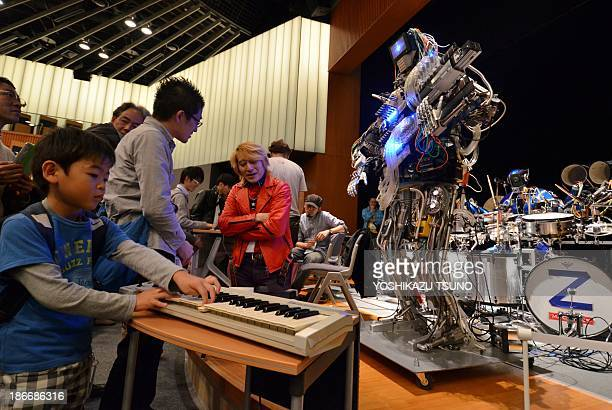 A boy plays a keyboard to control robot guitarist 'Mach' a member of a robot rock band 'ZMachines' during the two day art and technology event 'Maker...