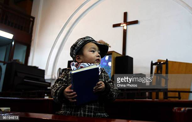 A boy plays as people attend a Christmas Eve mass at a church on December 24 2009 in Wezhou of Zhejiang Province China Christmas is not a public...