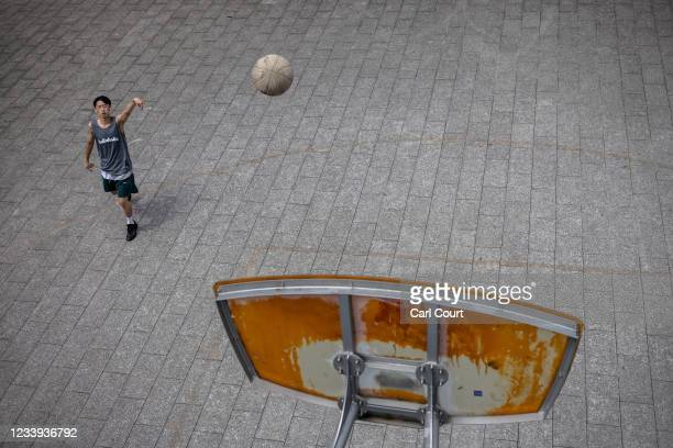 Boy plays basketball in Komazawa Olympic Park which hosted a number of venues for the 1964 Olympic Games, on July 12, 2021 in Tokyo, Japan. Now a...