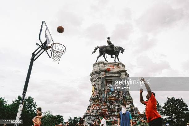 Boy plays basketball near the Robert E. Lee statue on June 23, 2020 in Richmond, Virginia. Gov. Ralph Northam ordered the statue taken down but a...