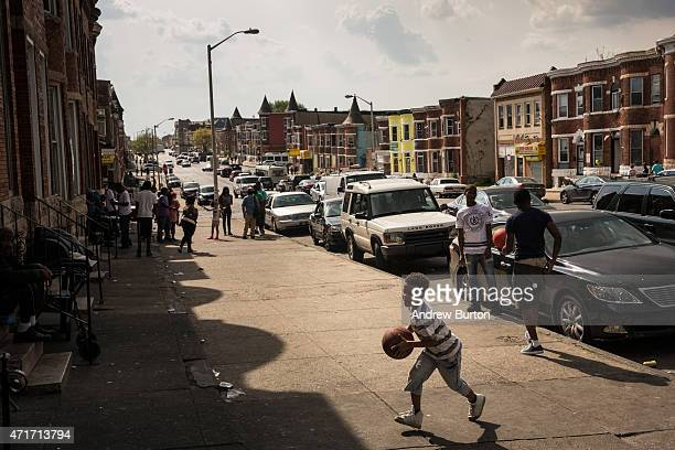A boy plays basketball on the street in the Sandtown neighborhood where Freddie Gray was arrested on April 30 2015 in Baltimore Maryland Gray was...