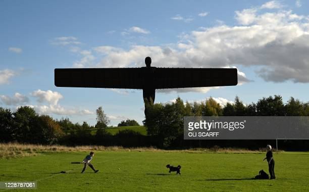Boy plays cricket near the iconic 'Angel of the North' sculpture, designed by Antony Gormley in Gateshead, northeast England in Gateshead, northeast...