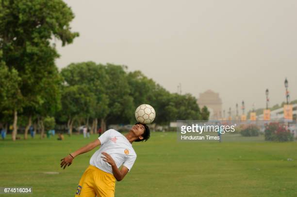 A boy plays football as clouds gather before a sudden downpour near India Gate on April 28 2017 in New Delhi India