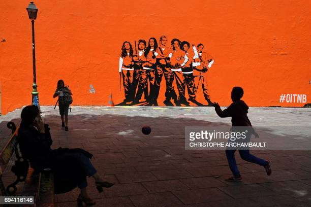 A boy plays football by a mural painting depicting the upcoming US series Orange Is the New Black to be shown on Netflix on June 9 2017 in Paris /...