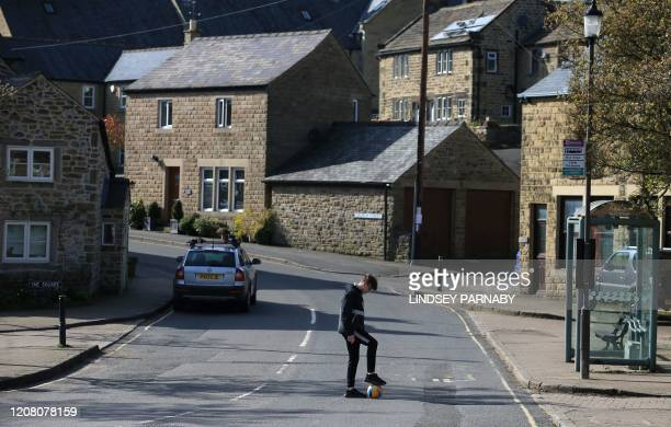 A boy plays football in a quiet street in the village of Eyam in Derbyshire northern England on March 23 2020 In the 17th century the inhabitants of...