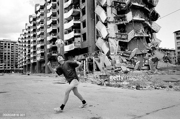 Bosnia Sarajevo June 1996 A boy plays football in front of a collapsed and bomb damaged apartment block in Sarajevo During the 47 months between the...