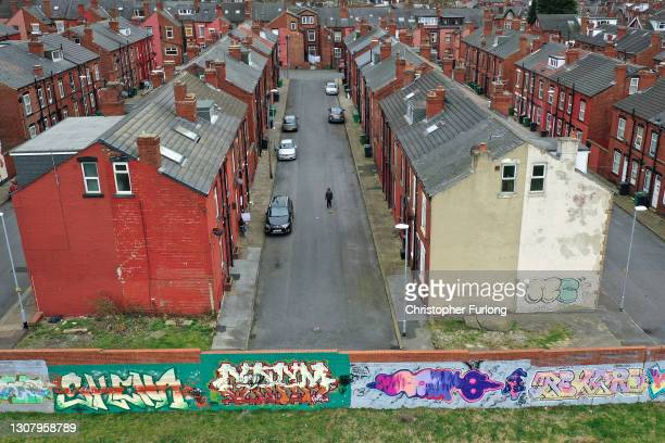 Boy plays football in the street next to traditional back to back homes in Beeston on March 19, 2021 in Leeds, United Kingdom.
