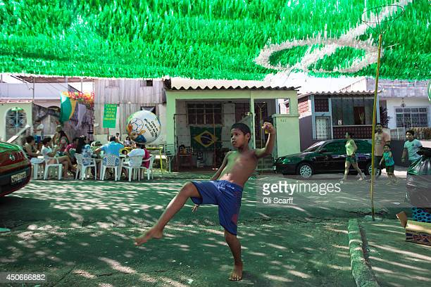 Boy plays football on Rua Santa Isabel which is covered with colourful streamers to celebrate the FIFA World Cup on June 15, 2014 in Manaus, Brazil....