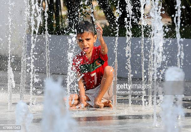 A boy plays in a fountain in city park on World Water Day March 22 2014 in Surabaya Indonesia Focusing on water and energy World Water Day recognizes...