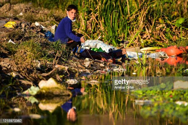 Boy plays in a garbage dump in front of a river contaminated with sewage and wastewater in Villa Itati on May 28, 2020 in Quilmes, Argentina. First...