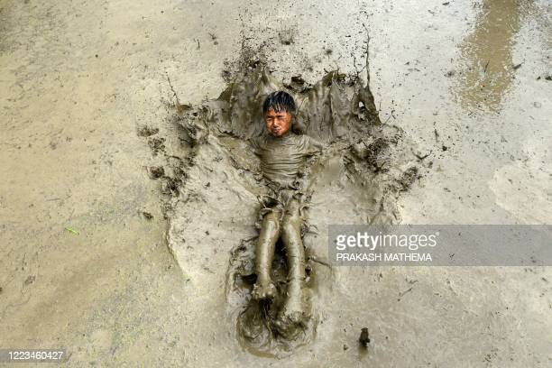TOPSHOT A boy plays in a rice paddy field during National Paddy Day which marks the start of the annual rice planting season in Tokha village on the...