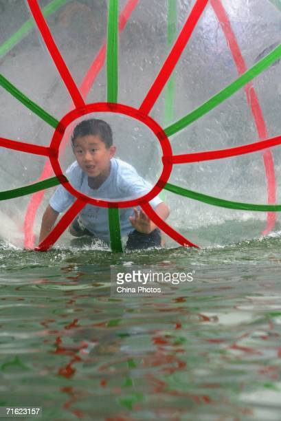 A boy plays in a water walking ball at Yuyuantan Park on August 10 2006 in Beijing China The ball that is 25 meters in diameter and filled with...