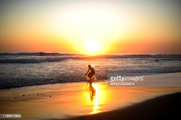 Boy plays in the ocean as the sun sets on the beach of San Blas on December 1, 2019 in La Libertad, San Salvador, El Salvador.
