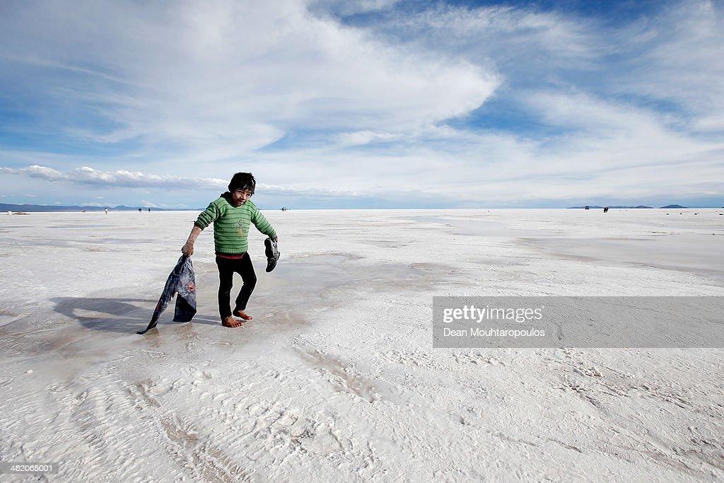 A boy plays in the salt at the Salar de Uyuni or Uyuni Salt Flat during Day 7 of the 2014 Dakar Rally on January 11, 2014 in Uyuni, Bolivia.