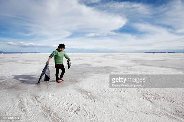 A boy plays in the salt at the Salar de Uyuni or Uyuni Salt Flat during Day 7 of the 2014 Dakar Rally on January 11 2014 in Uyuni Bolivia