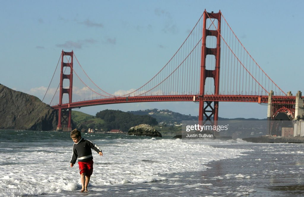 A Boy Plays In The Water At Baker Beach Near Golden Gate Bridge March 25