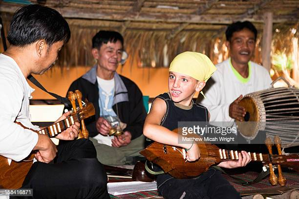 A boy plays music with locals